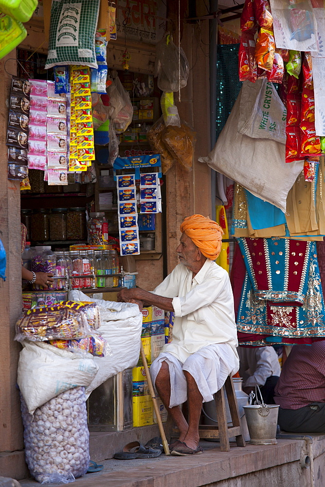 Indian shopkeeper in his food shop and general store in village of Rohet in Rajasthan, Northern India