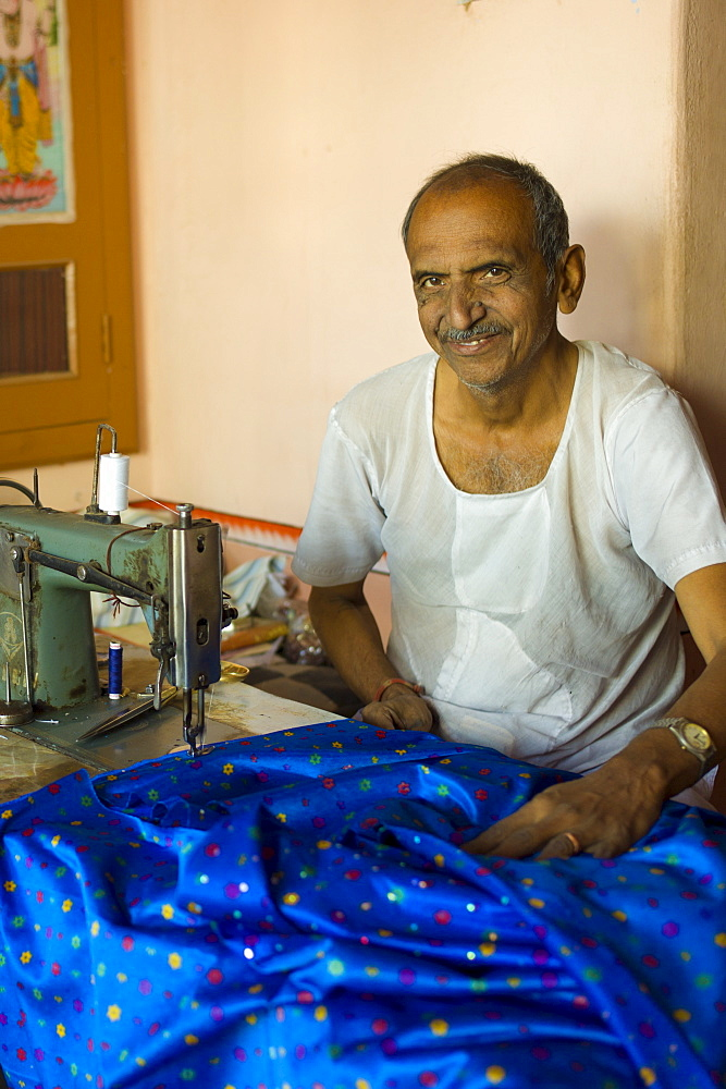 Indian man with traditional sewing machine making sari in Rajasthani colourful silk fabric in Narlai village in Rajasthan, Northern India