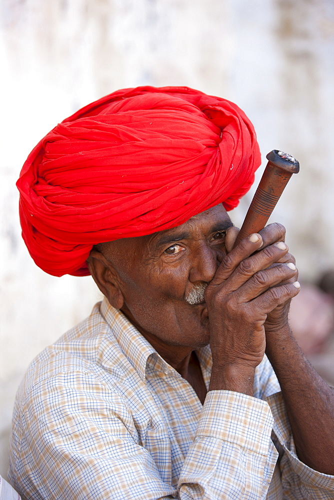 Indian man wearing Rajasthani turban smokes traditional clay pipe in Narlai village in Rajasthan, Northern India