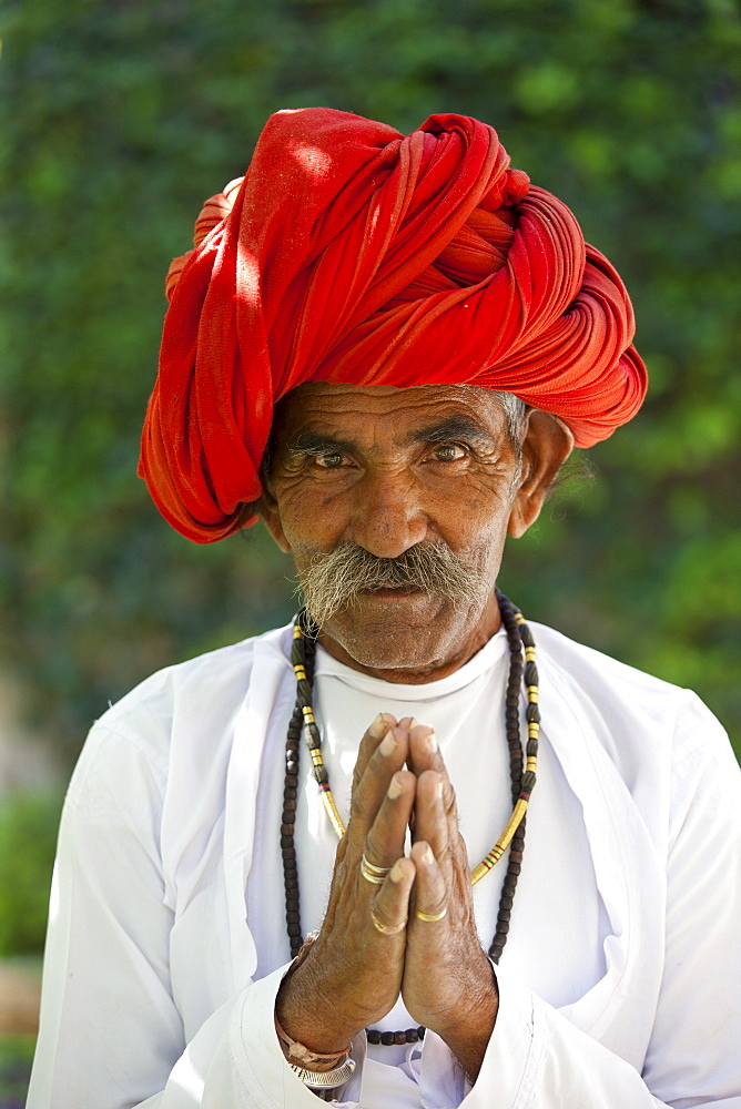 Traditional Namaste greeting from Indian man with traditional Rajasthani turban in village in Rajasthan, India