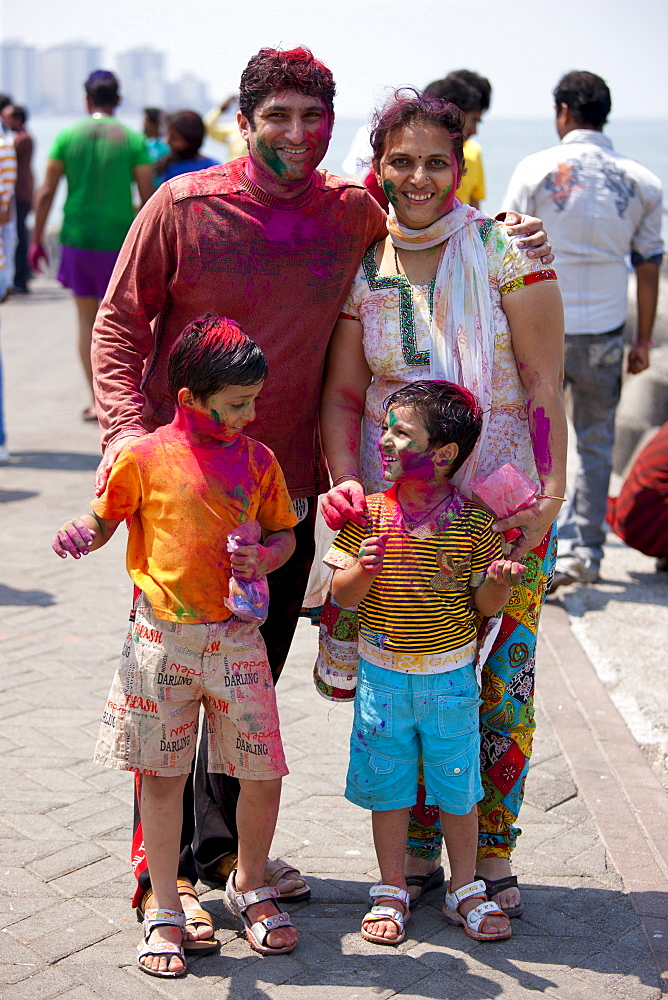 Indian family celebrating annual Hindu Holi festival of colours with powder paints at Nariman Point in Mumbai, formerly Bombay, India