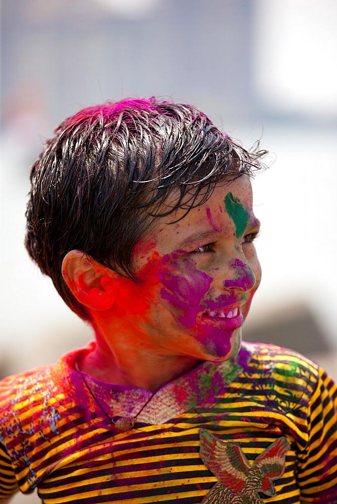 Young Indian boy celebrating annual Hindu Holi festival of colours with powder paints in Mumbai, formerly Bombay, Maharashtra, India