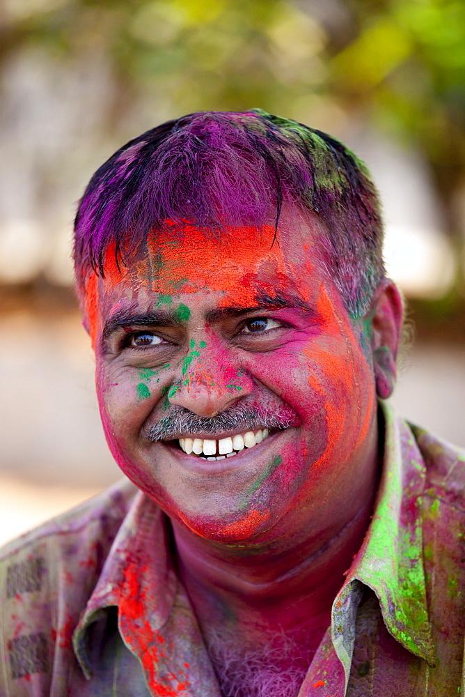 Indian man celebrating annual Hindu Holi festival of colours with powder paints in Mumbai, formerly Bombay, Maharashtra, India