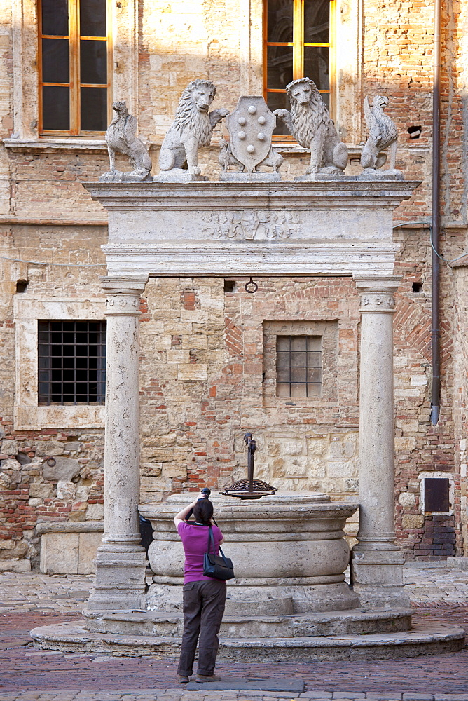 Tourist photographs well of griffins and lions by Palazzo del Capitano del Popolo in Piazza Grande, Montepulciano, Tuscany, Italy