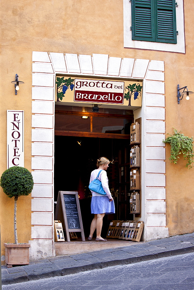 Woman shopping in Grotta del Brunello wine shop in Costa di Piazza Garibaldi in old hill town of Montalcino, Val D'Orcia, Tuscany, Italy