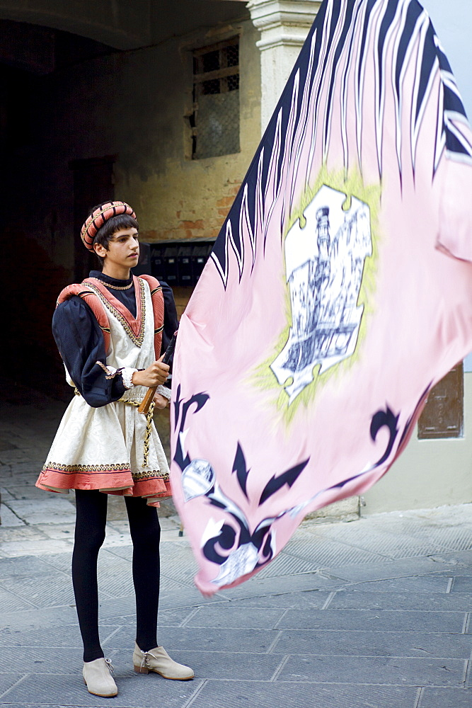 Contrada young man in livery costume at traditional parade in Asciano, inTuscany, Italy