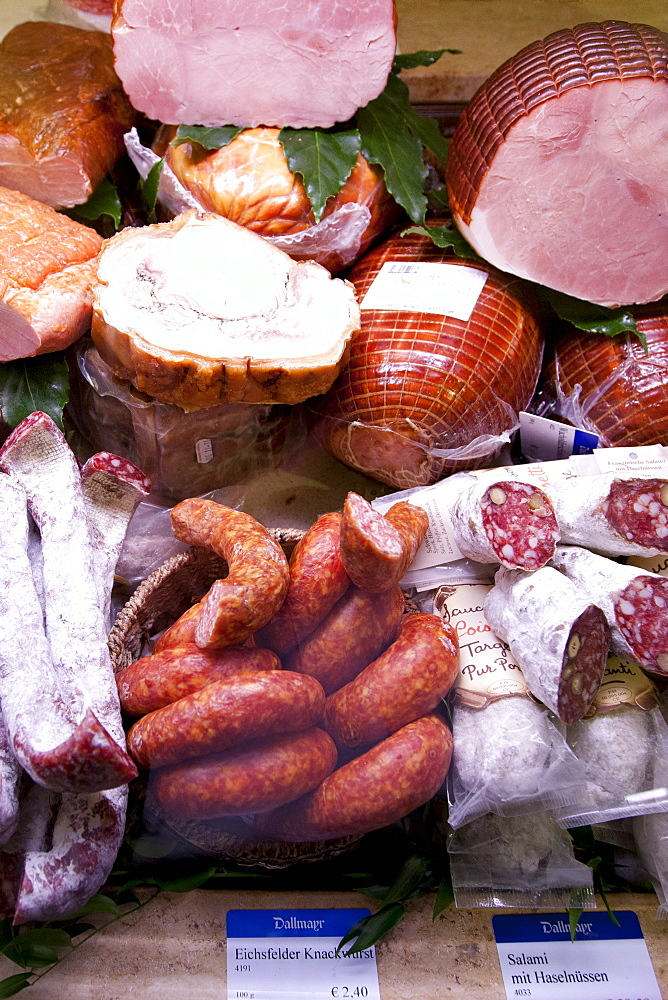 Shop display of cured meats, hams, pork sausages, salami, at Dalmayr food shop and delicatessen in Munich, Bavaria, Germany