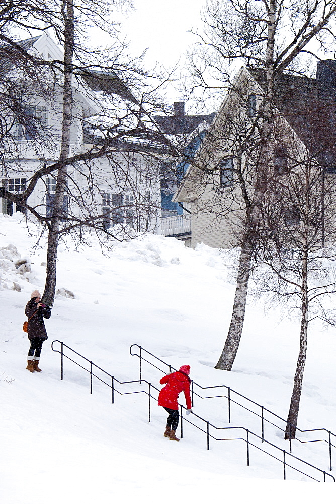 Young woman takes photographs as her friend hangs onto handrail to avoid slipping on the steps in snowy Tromso, Norway