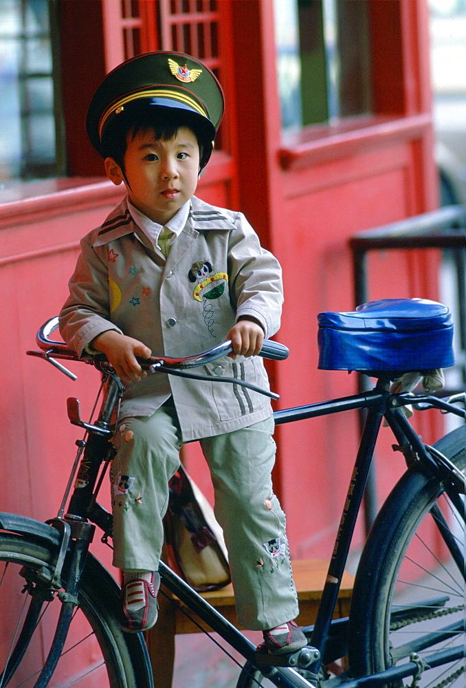 Boy on a bike wearing uniform in Beijing, China