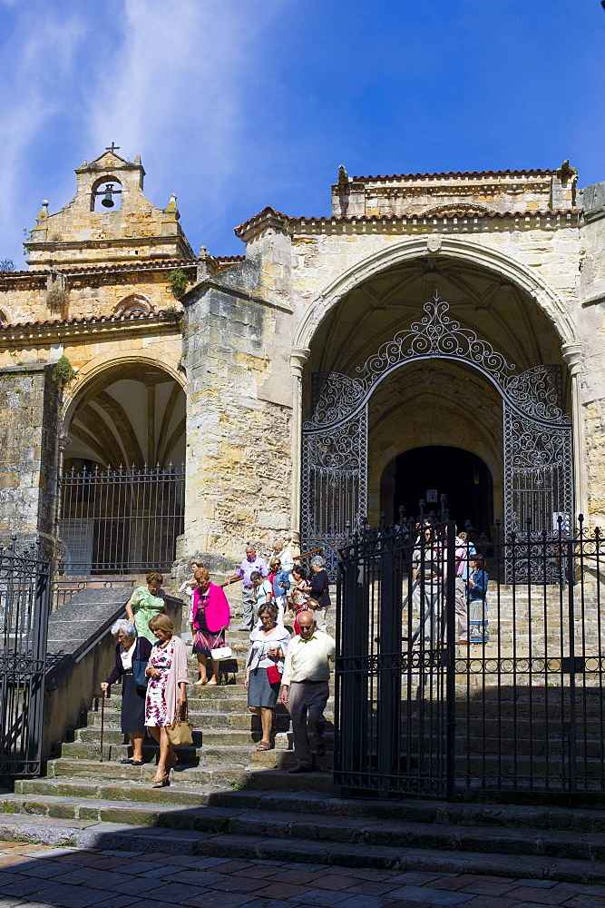 Roman Catholic worshippers leaving Mass in the church Iglesia Santa Maria de la Asuncion, Laredo, Cantabria, Spain