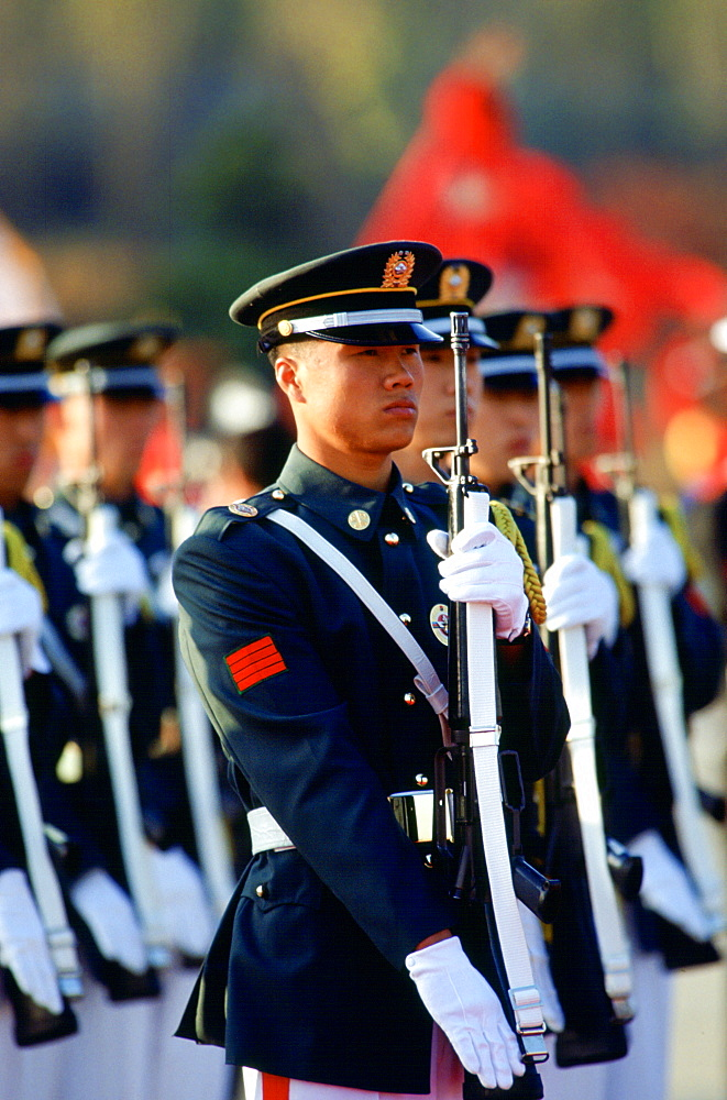 Soldiers on parade in South Korea raise their rifles