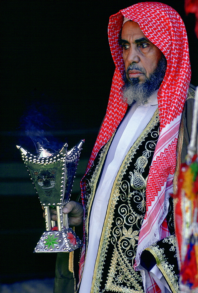 Bedouin man holding a smoking incense burner, Saudi Arabia