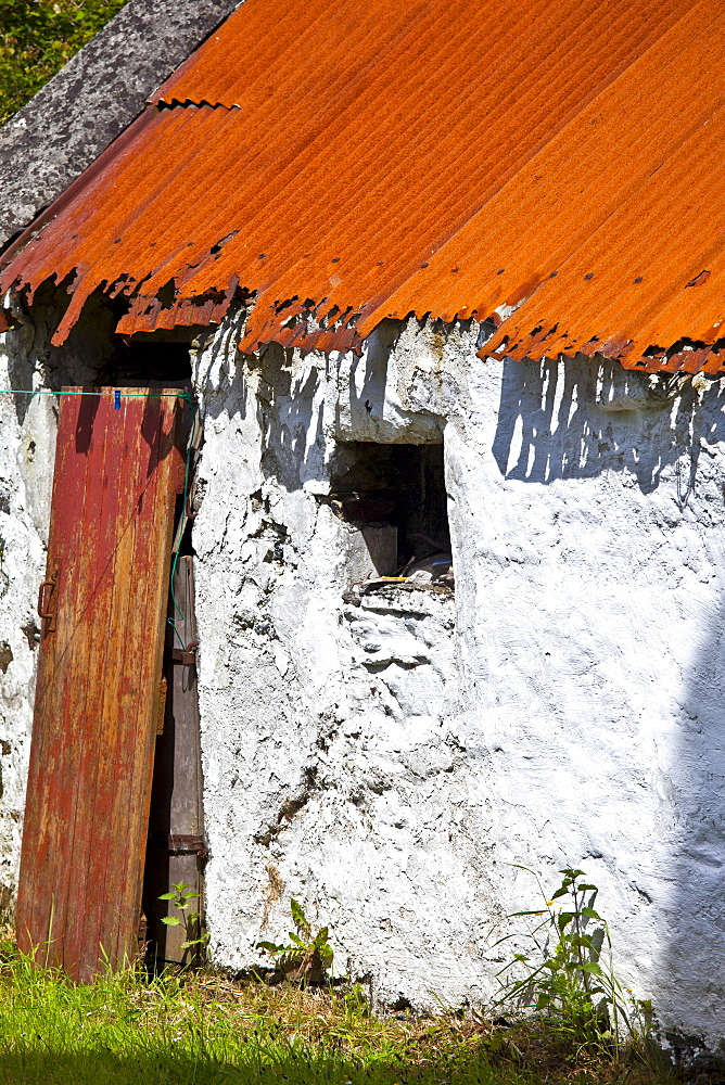 Whitewashed barn with rusty corrugated iron roof in County Cork, Ireland