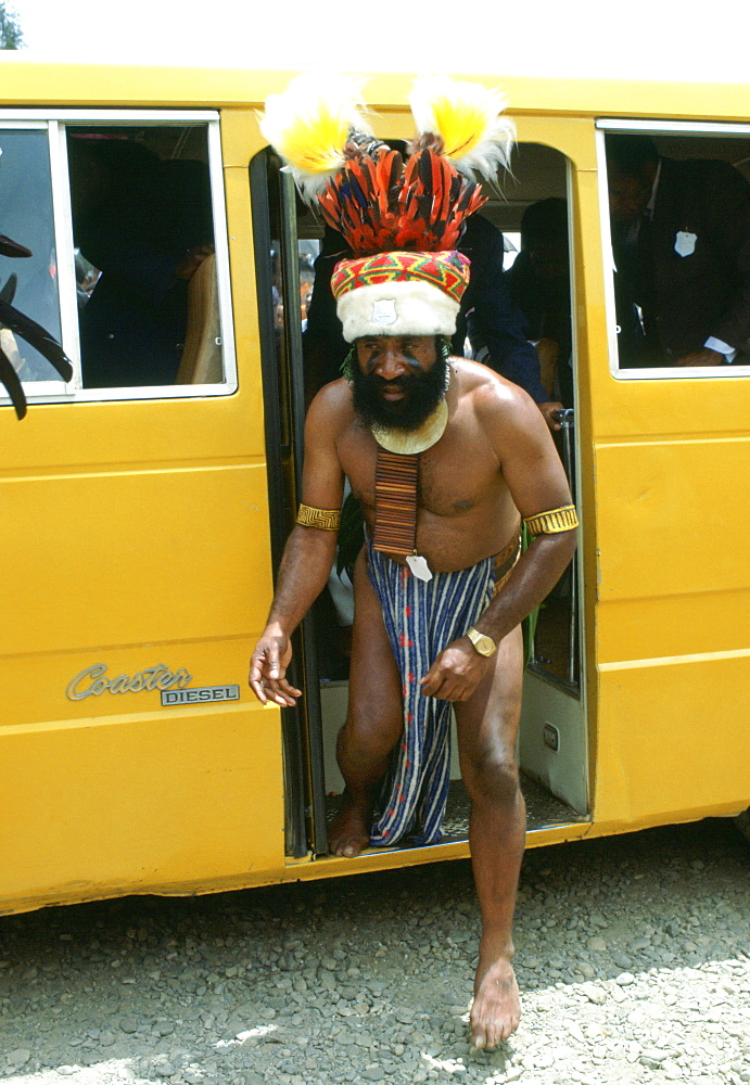 Bearded tribesman in feathered headdress steps from a modern minibus during  a gathering of tribes at Mount Hagen in Papua New Guinea