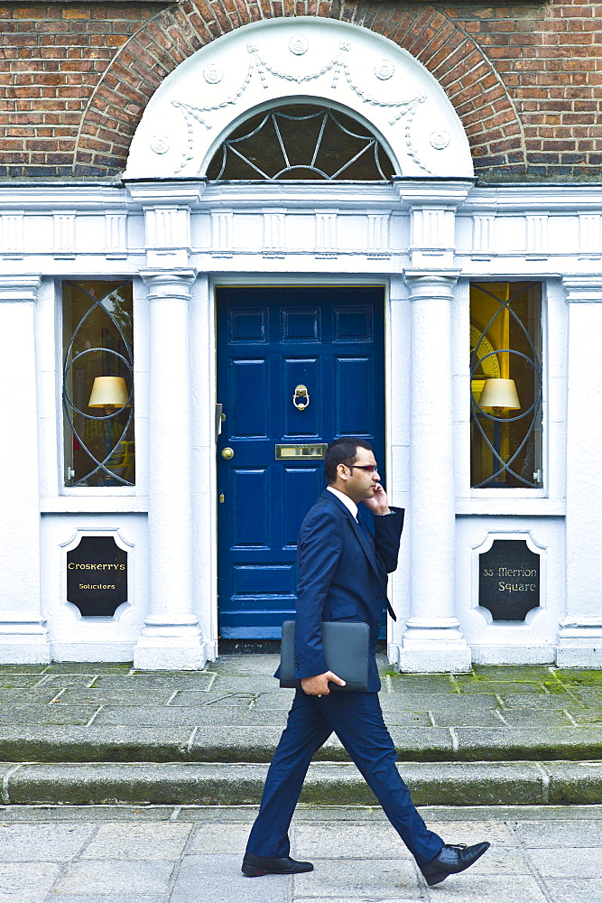 Businessman using cellphone passes traditional doorway with fanlight windows in Merrion Square, Dublin, Ireland
