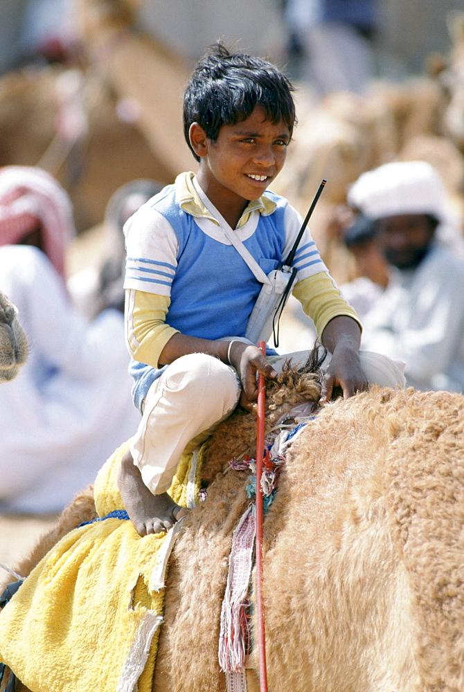 Boy jockey camel racing with walkie talkie radio early cellphone in Al Ain, Abu Dhabi, United Arab Emirates, Middle East