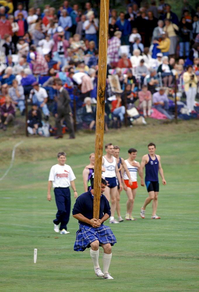 Scottish strongman in tartan kilt tossing the caber at the Braemar Royal Highland Gathering, the Braemar Games in Scotland