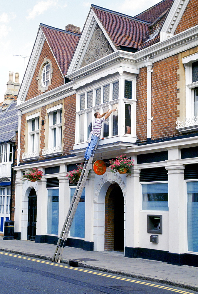 Windows being cleaned at Coutts and Co. bank which provides banking for pupils at nearby Eton College public school, England, UK