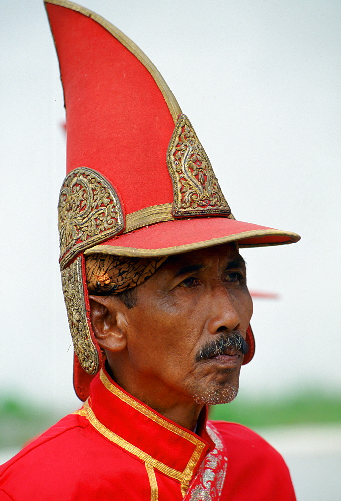 Courtier at the Sultan's Palace,Yogyakarta, Indonesia wearing a pointed hat and bright red uniform