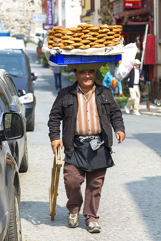 Typical Simitci Turkish man selling simit, Turkish sesame bread rings, in streets of Istanbul, Turkey, Europe