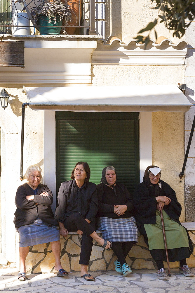 Elderly Corfiot women wearing traditional black clothes sitting relaxing in village square of Krini, Corfu, Greek Islands, Greece, Europe - 1161-8664