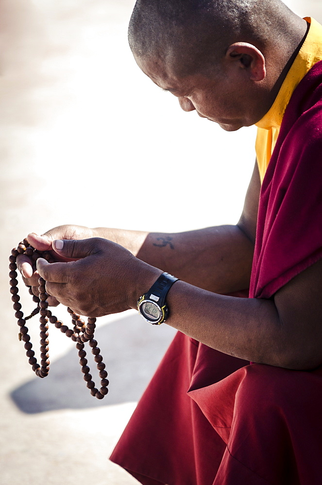 A Buddhist monk prays using a set of prayer beads (Japa Mala), Bodhnath stupa, Bodhnath, Nepal, Asia