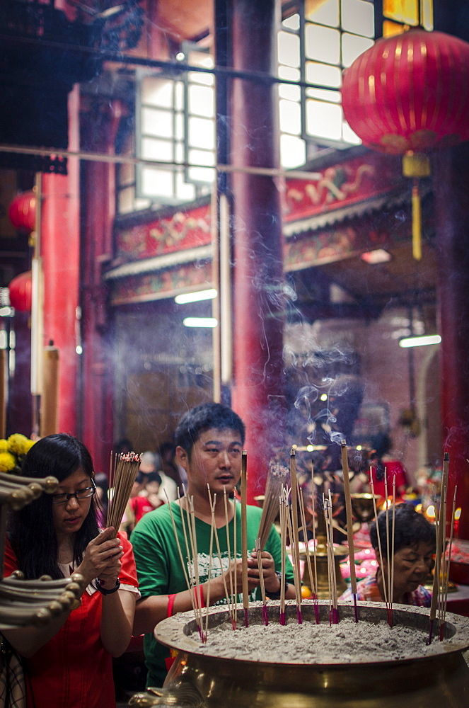 A man and women light incense sticks and pray during Chinese New Year celebrations, Sze Ya Temple, Chinatown, Kuala Lumpur, Malaysia, Southeast Asia, Asia - 1163-11