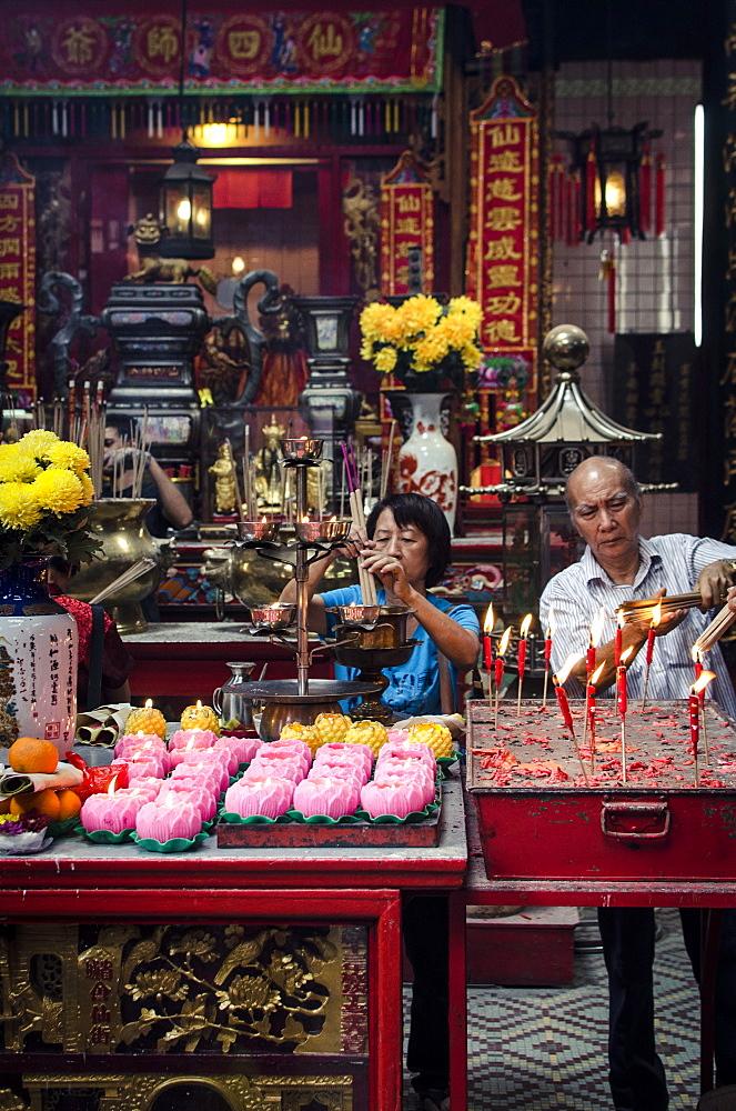A man and women light incense sticks during Chinese New Year celebrations, Sze Ya Temple, Chinatown, Kuala Lumpur, Malaysia, Southeast Asia, Asia
