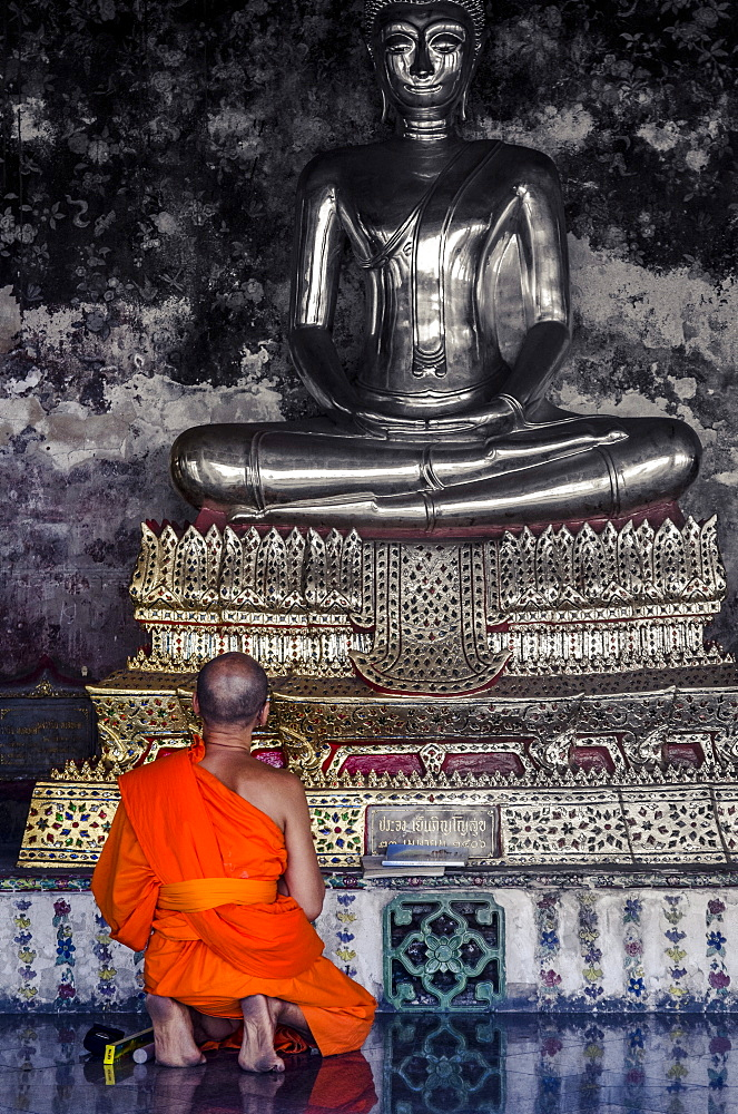 A monk prays in front of a golden Buddha, Wat Suthat, Bangkok, Thailand, Southeast Asia, Asia  - 1163-32