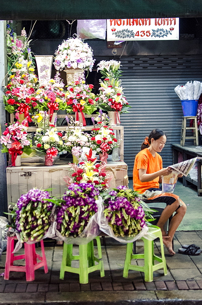 A flower seller reads the morning newspaper, Pak Khlong Flower Market, Bangkok, Thailand, Southeast Asia, Asia  - 1163-33