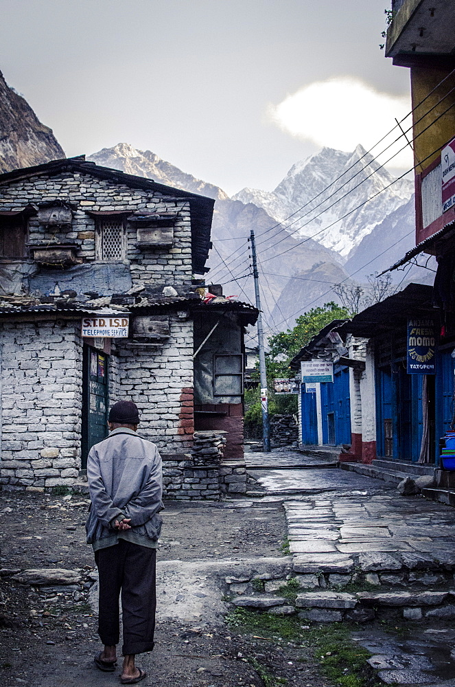 A man walks through Tatopani, with Nilgiri Peak, 7061m, in the background, Annapurna Conservation Area, Nepal, Himalayas, Asia