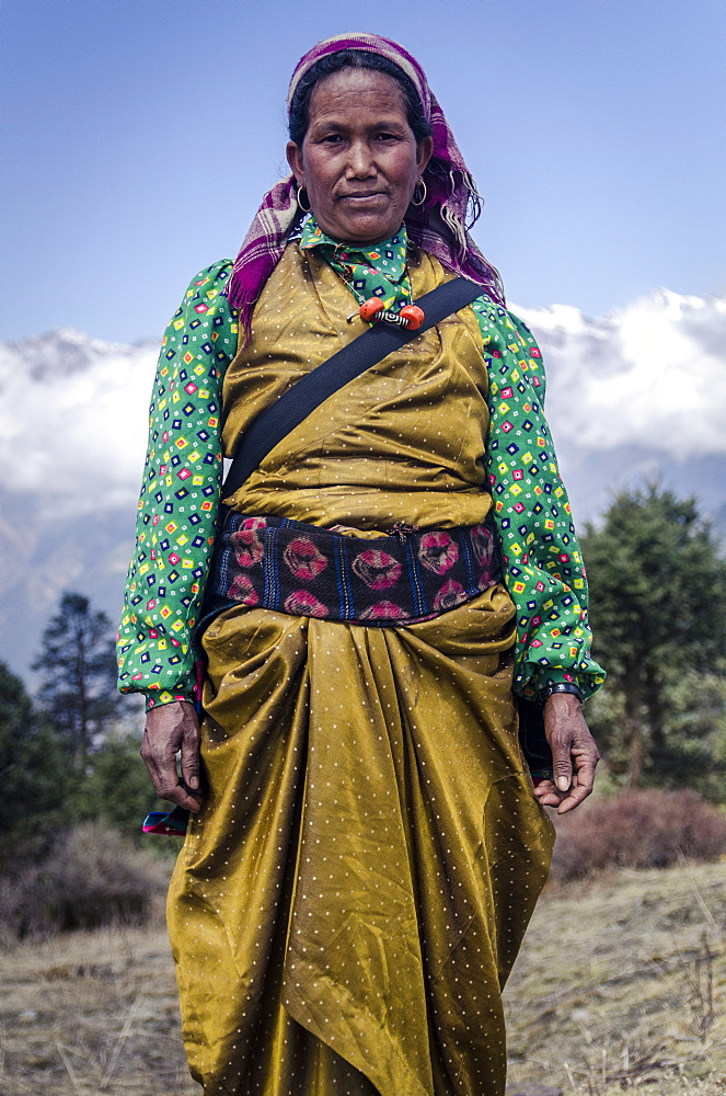 A woman wearing traditional dress in front of the Himalaya mountains, Mere Danda, Helambu, Nepal, Asia - 1163-92