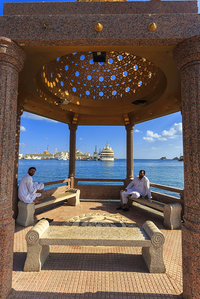 Seated Omani men wearing traditional dishdasha on Mutrah Corniche, with view to Al Said Royal Yacht, Muscat, Oman, Middle East