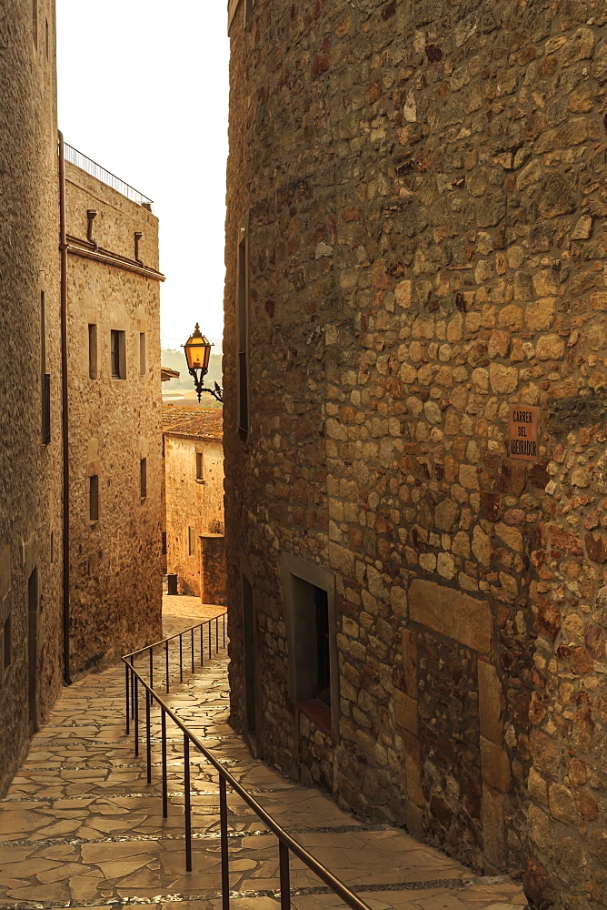 Steep and narrow winding street in gorgeous medieval hilltop walled village, Pals, Baix Emporda, Girona, Catalonia, Spain, Europe