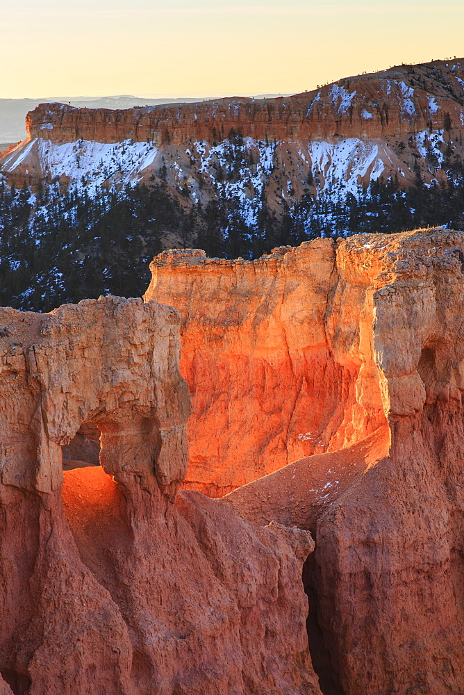 Rocks lit by strong dawn light, snowy backdrop, Queen's Garden Trail at Sunrise Point, Bryce Canyon National Park, Utah, United States of America, North America