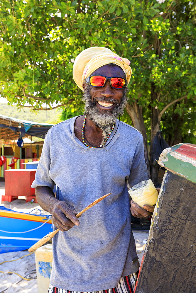 Grinning man repairs boat, colourful Saltwhistle Bay, Mayreau, Grenadines, St. Vincent and The Grenadines, Windward Islands, West Indies, Caribbean, Central America