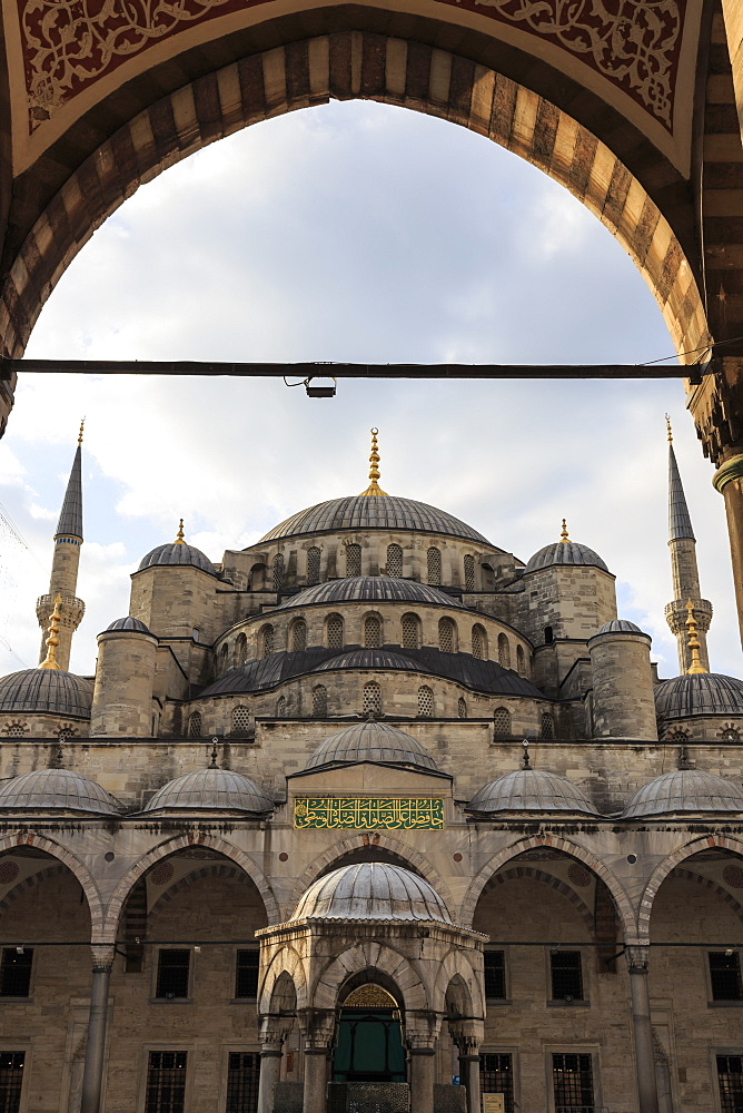 Blue Mosque under a partially cloudy sky through an ornate archway, golden August early morning, Sultanahmet, Istanbul, Turkey, Europe