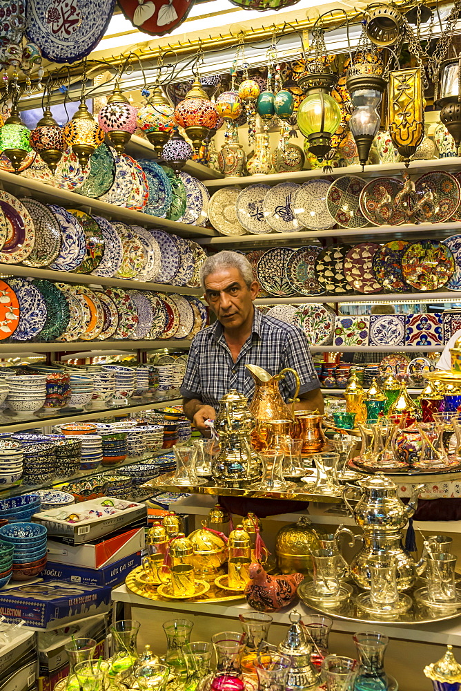 Seller (vendor) of traditional Turkish ceramics, glassware and tea sets in his shop, Grand Bazaar, Istanbul, Turkey, Europe