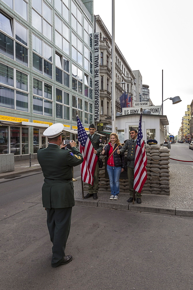 Tourist has photo taken with uniformed actor border guards, Checkpoint Charlie, Mitte, Berlin, Germany, Europe