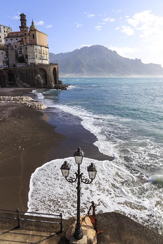 Fancy street lamp, rusty anchor and wave breaking on beach, distant church, Atrani, near Amalfi, Costiera Amalfitana (Amalfi Coast), UNESCO World Heritage Site, Campania, Italy, Europe