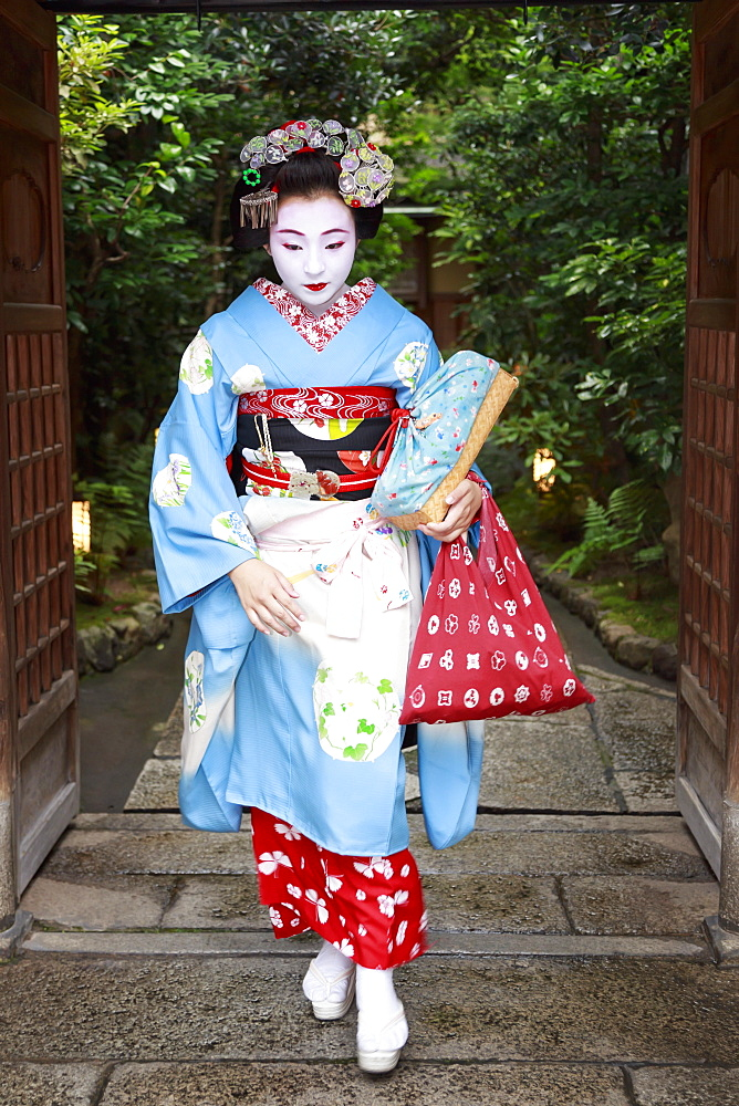 Maiko, apprentice geisha, leaves okiya (geisha house) through garden gate for evening appointment, Gion, Kyoto, Japan, Asia