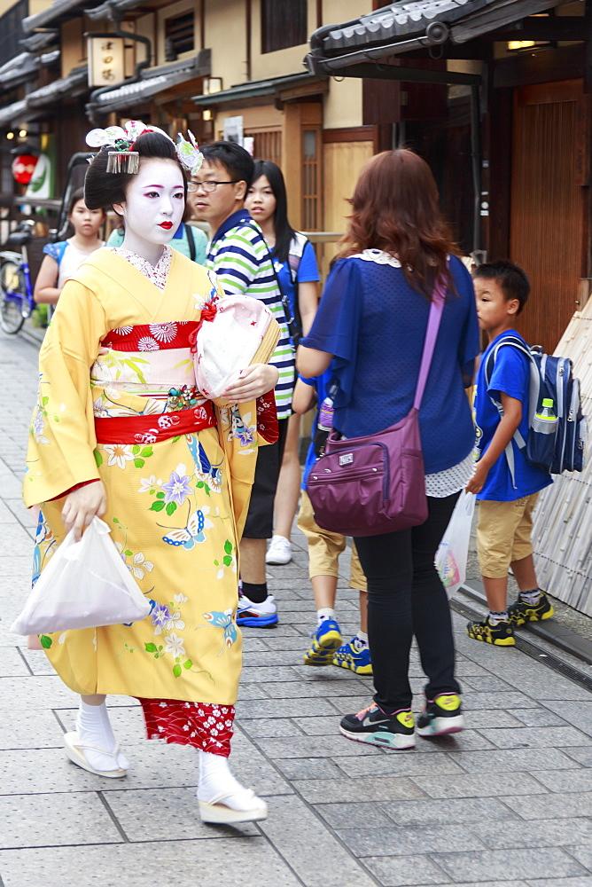Maiko, apprentice geisha, walks to evening appointment through tourist crowd, Hanami-koji street, Gion, Kyoto, Japan, Asia