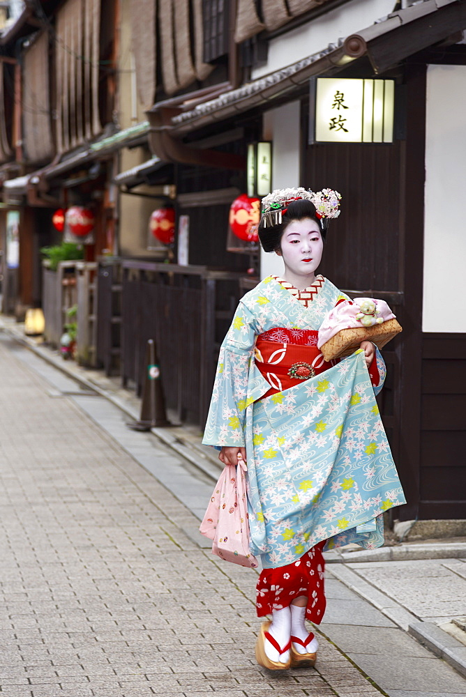 Maiko, apprentice geisha, walks to evening appointment past traditional wooden buildings, Gion, Kyoto, Japan, Asia