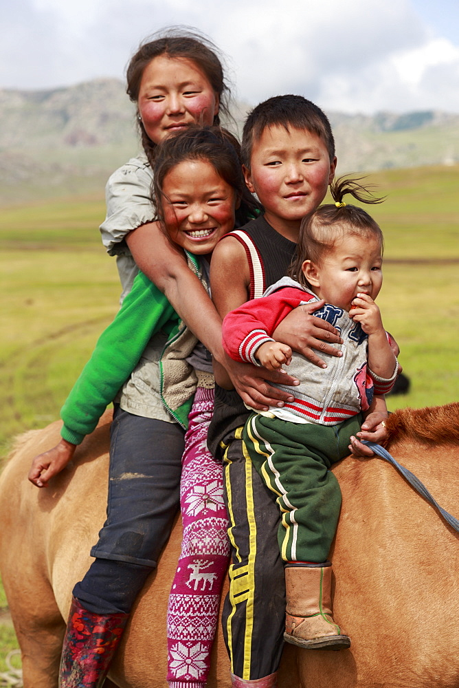 Portrait of four smiling and happy nomad siblings on their tame horse at summer nomad camp, Khujirt, Uvurkhangai, Central Mongolia, Central Asia, Asia