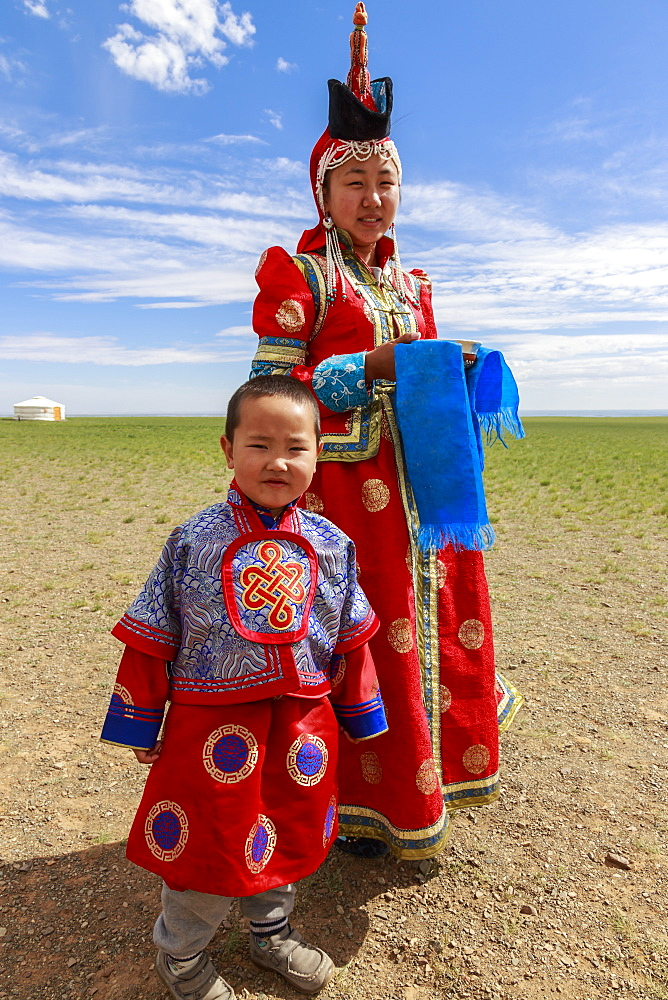 Woman and child in traditional dress (deel), silver bowl for milk greeting, near ger, Gobi desert, Bulgan, Omnogov, Mongolia, Central Asia, Asia