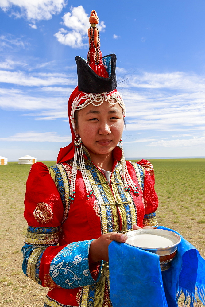 Woman in red deel and pointed hat with silver bowl of milk to welcome visitors, Gobi desert, near Bulgan, Omnogov, Mongolia, Central Asia, Asia