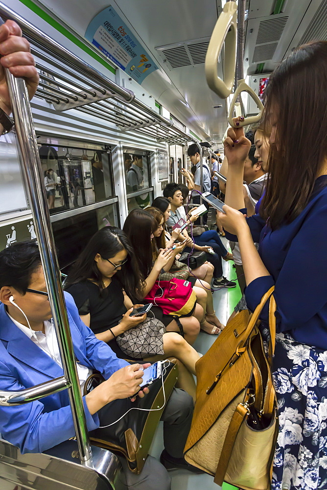 Smartly dressed commuters on the busy subway looking at their phones and e-devices, Seoul, South Korea, Asia