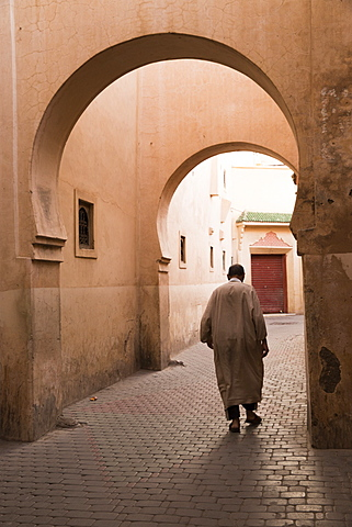Man walking down narrow alley by Ali Ben Youssef Medersa, Old Medina, Marrakesh (Marrakech), Morocco, North Africa