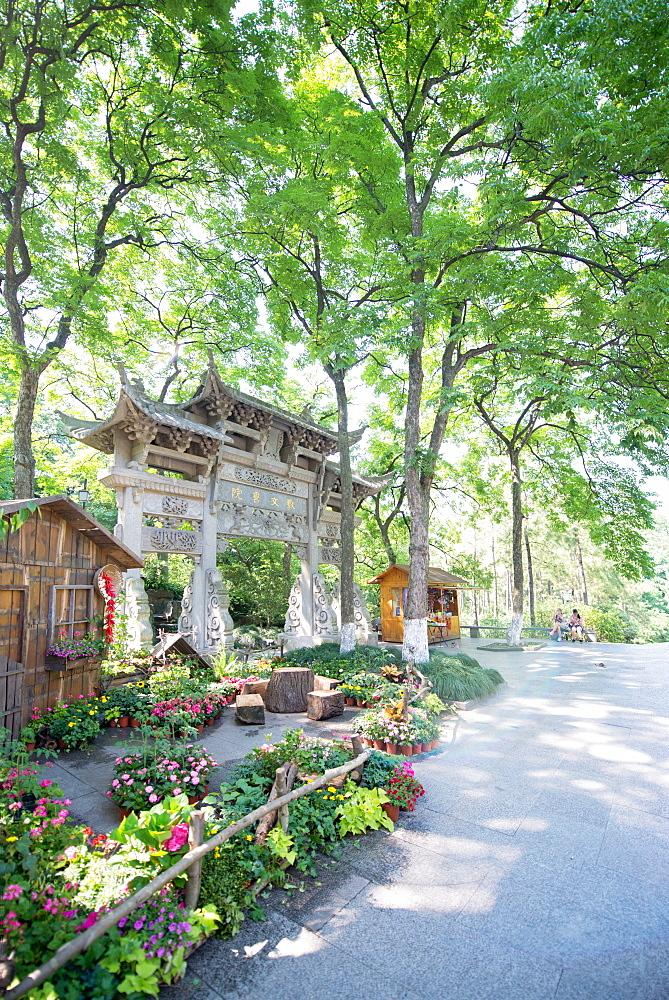 Traditional Chinese stone gate, lush surroundings and floral decorations at Wansong Academy, Hangzhou, Zhejiang, China, Asia