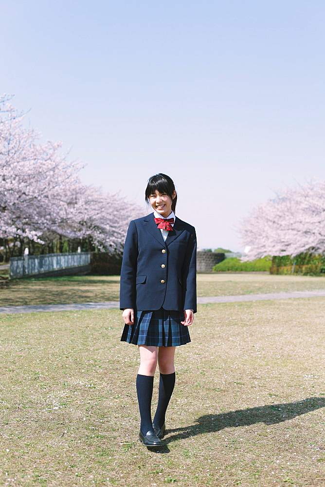 Japanese schoolgirl in her uniform with cherry blossoms in the background